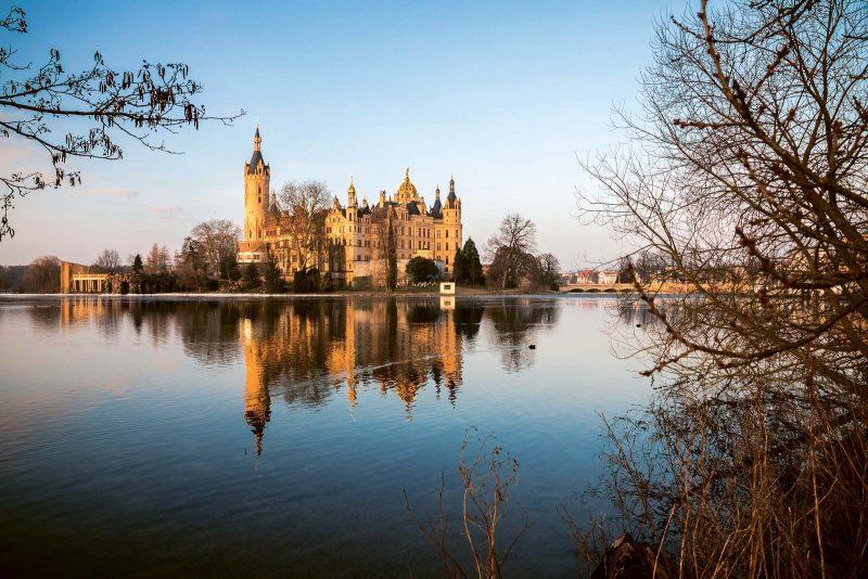 Schloss Schwerin: malerisch auf einer Insel im Schweriner See gelegen. Skulptur »Vogelzug« von Künstler Jo Jastram am Ziegelsee.