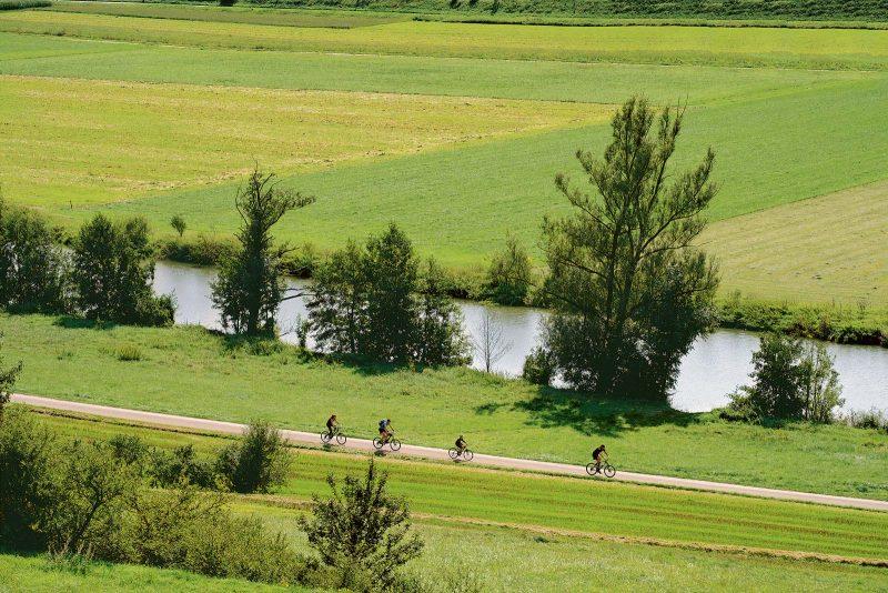 Der Fluss ist ein treuer Begleiter. Radler bei Dollnstein im Naturpark Altmühltal